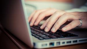 Närbild av händer som använder en bärbar dators tangentbord.
