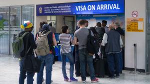 Turister på flygplats köar för att skaffa visum.