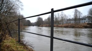 En bild på en å  och ett staket som står bredvid den.