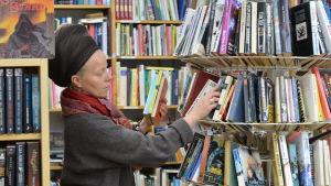En kvinna står omgiven av böcker och sorterar böcker som är uppradade i en rund ställlning
