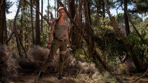 Lara Croft poserar i skogen.