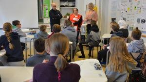 Tre vuxna står framför en fullsatt klass