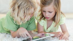 Två flickor ligger på golvet och spelar på en pekplatta.
