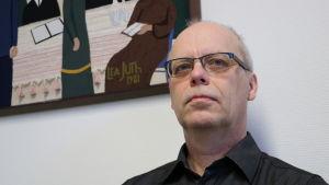 En man med glasögon sitter invid en vit vägg.