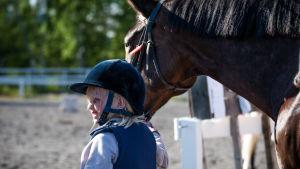 En flicka leder en stor häst.