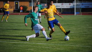 Två fotbollsspelare fajtas om bollen.