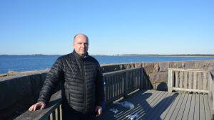 En bild på en man som står vid havet. Han lutar mot ett staket. Mannen heter Anders Ahlvik och han är vd för Hangö hamn