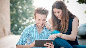 Ung man och kvinna tittar på pekplatta