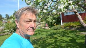 En man i en blå t-skjorta står i en trädgård med blommande äppelträd
