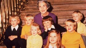Äldre kvinna och sju barn sitter på trappa