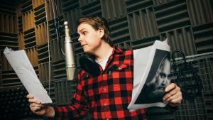 Mies lukemassa tekstiä mikrofoniin studiossa. Kädessä papereita ja Gösta Sundqvistin valokuva.