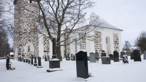 En stor vit stenkyrka. Framför kyrkan finns flera gravstenar. Det är vinter och snö på marken.