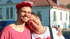 Elias Edström kramar om Larrie Griffis framför ett gammalt hus.