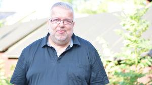 En glasögonprydd man står utomhus. Han ler mot kameran. Det är sommar.