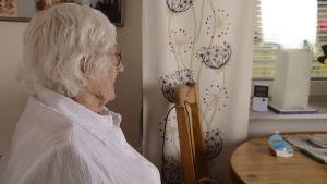 Äldre kvinna i profil som sitter vid ett fönster.