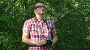Niclas Rantala står i skogen med kamera i handen.