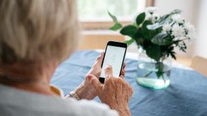 Eläkeikäinen nainen näppäilee kännykän pin-koodia.