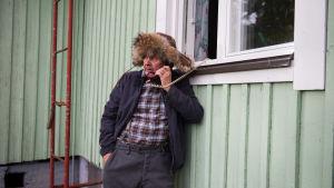 Kverulanten står på gården och talar i trådtelefonen vars sladd hänger uyt genom köksfönstret..