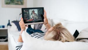 Kuvassa mummo makaa sohvalla ja katsoo ohjelmaa tabletilla