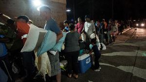 Personer som evakuerat undan orkanen Florence står i kö utanför en skola.