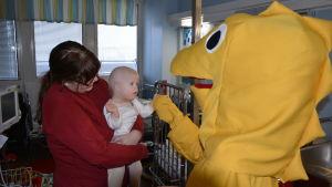 En stor gul Svenni-figur skakar hand med en baby och mamma på ett sjukhus.