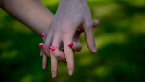 Två unga personer håller varandra i händerna.