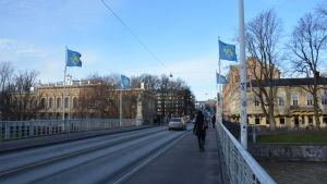 Vy över Aurabron, kvinna går över bron och en bil kör över bron.