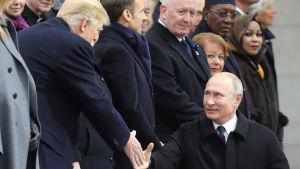Presidenterna Trump och Putin skakar hand.