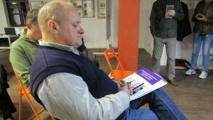 En man sitter på en orange stol med en bok i famnen.