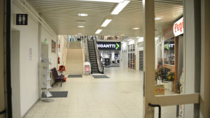 En bild från insidan av ett köpcentrum. På bilden syns en rulltrappa och två affärer.