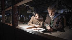 Otto (Amos Brotherus) och Olavi (Heikki Nousiainen) sitter i arkivet och tittar på gamla utställningskataloger.