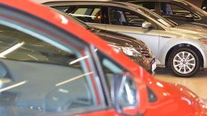 Nya bilar inne i en bilaffär.