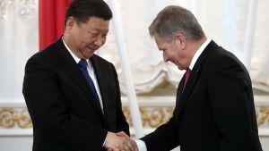 Sauli Niinistö och Xi Jinping skakar hand i presidentslottet i Finland år 2017.