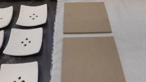 Kakelbitar som skurits ur lera och som torkar på ett bord.