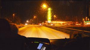 Genom framfönstret på en buss synns Gammelby ABC i mörkret.