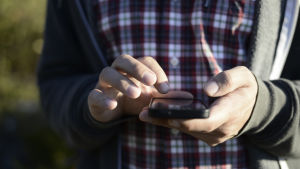 En person håller en smarttelefon i handen och håller fingret ovanpå skärmen.