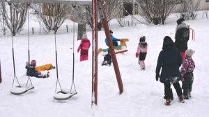 lekpark med barn och vuxna i snö