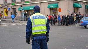 polis i gul väst står vid gathörn i Åbo. Folk passerar på trottoaren