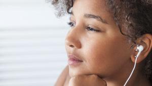 En tjej lyssnar på nåt i hörlurar och ser drömsk ut.