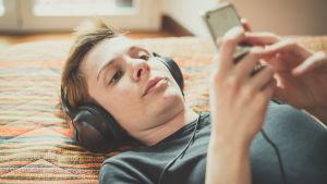 Kvinna med kort hår ligger på säng med hörlurar och lyssnar på nåt från mobilen.