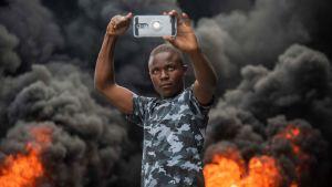En demonstrant tog en selfie mot bakgrunden av brinnande bildäck i Port-au-Prince på söndagen.
