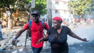 Demonstranter sprang undan tårgasen under lördagens protester i Port-au-Prince.