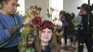 Vieno Motorsin taiteilija Laura Pehkonen tekee Jenna Rönkölle susikruunun.