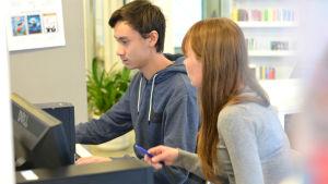 Alexander Engberg sitter vid en dator och får hjälp av Linda Loimijoki.