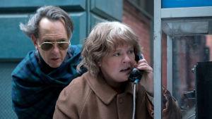 Richard E. Grant ja Melissa McCarthy puhelinkopin luona. Kuva elokuvasta Can You Ever Forgive Me?