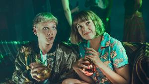 Oona ja Arttu istuvat sohvalla bilevaatteissaan, käynnissä on juhlat ja kuvassa on vihreä valaistus.