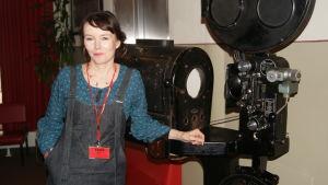 Marja Helander poserar vid gammal filmkamera.
