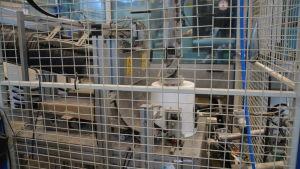 Hink tillverkas på fabrik. Den vita hinken placeras upp och ner av en robot.