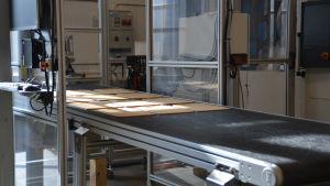 Skärbrädor på ett rullband i en fabrik.