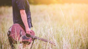 anonyymi mies seisoo pellolla kitara kädessään
